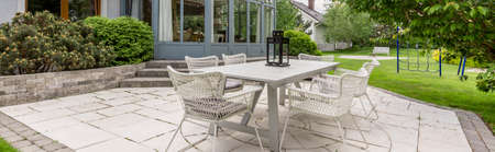 empedrado: White rattan garden table with set of chairs in a paved backyard of a luxurious villa