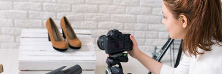 Panoramic photo of a young photographer taking shots of high heels in a bright atelier