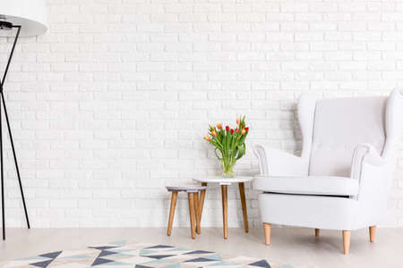 Shot of a white room with a big armchair and a brick wall
