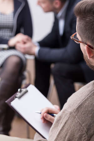 Close-up of a therapist holding a flipboard during a session with a couple in the blurred background
