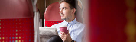 gente exitosa: Young businessman is drinking coffee in the train