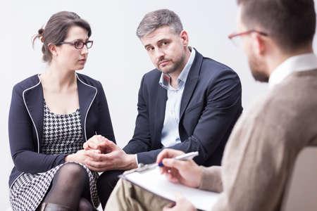 若い、スマートに身を包んだカップル療法会議の間に互いの手を繋いで