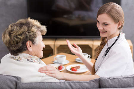 Cheerful medic with stethoscope during home visit and her senior patient