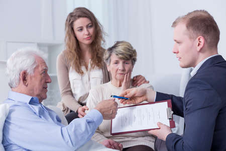 Hospital room where a lawyer is handing an old man a testament to sign in the presence of the relatives