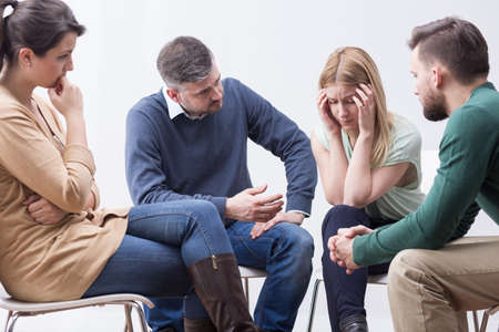 devastated: Young, devastated woman talking to other members of support group Stock Photo