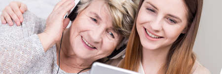 grandkids: Older grandmother listening her young granddaughters music on headphones from tablet