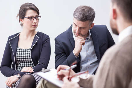 Shot of an elegantly dressed couple looking angrily at each other during a conversation with a counselor
