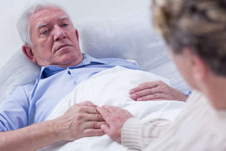 palliative: Close-up of a dying elderly man in a hospital bed, holding his wifes hand