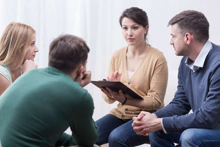 terapia de grupo: mujer joven con una Flipboard dirigir una discusión entre un grupo de personas que se sientan en un círculo Foto de archivo