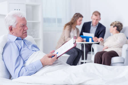 testament schreiben: Elderly man in a hospital bed analysing the documents he is about to sign, with his family in the blurred background