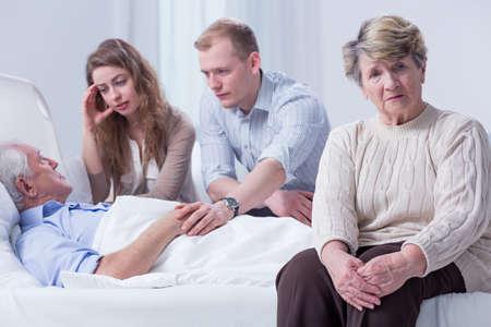enfermo: Familia, incluyendo nietos, visitar a un anciano en un hospital, con su esposa en dificultades en el primer plano