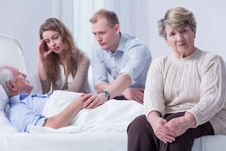 grandkids: Family, including grandchildren, visiting an elderly man in a hospital, with his distressed wife in the foreground