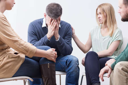 peers: Young distressed man sitting among supportive peers, hiding his face in his hands Stock Photo