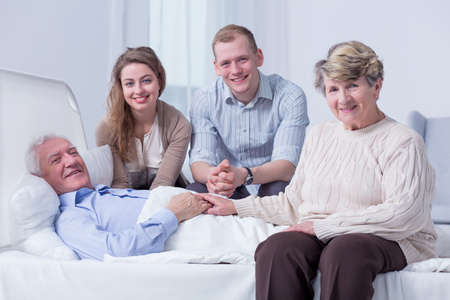 recovering: Smiling family members surrounding the bed of an old man in a very bright hospital room
