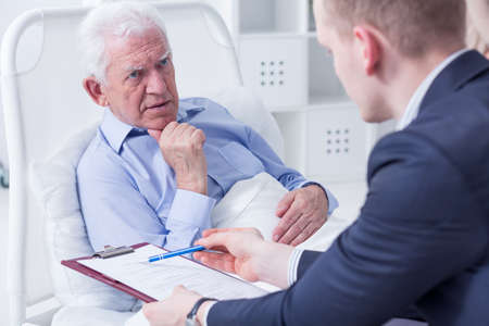 Senior man in a hospital bed about to sign his last will in the presence of the lawyer