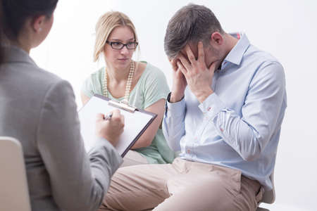 Close-up of a young couple during therapy session, the man hiding his face in his hands Stock Photo