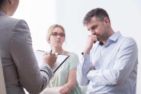 Disparo de un terapeuta teniendo femeninos notas durante la reunión con un joven matrimonio