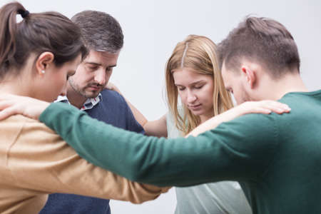 confess: Close-up of four people standing in circle with eyes closed, holding each others shoulders in a supportive pose