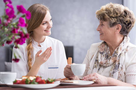 beside table: Senior woman and young nurse during home visit, sitting beside table and drinking coffee Stock Photo