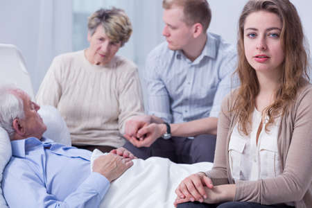 palliative: Worried young woman sitting by the hospital bed of her grandfather, with other family members in the blurred background Stock Photo