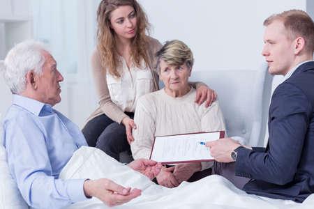 testament schreiben: Älterer Mann im Krankenhaus von Verwandten umgeben und Dokumente übergeben wurde er zu unterzeichnen weigert