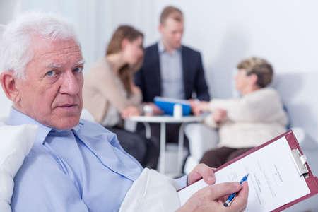 testament schreiben: Close-up von einem Mann in einem Krankenhausbett hält seine letzte wird er über sich anmelden Lizenzfreie Bilder