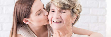 cheek to cheek: Close-up of young girl giving a kiss in cheek to her lovely happy grandmother