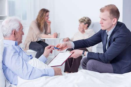 testament schreiben: Alter Mann in einem Krankenhausbett Dokumente werden �bergeben von einem Anwalt zu unterzeichnen neben ihm sa�