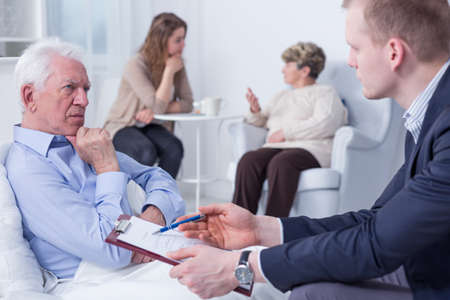 testament schreiben: Alter Mann in einem Krankenhausbett mit einem Notar sitzt neben ihm mit einem Klemmbrett und Dokumente Lizenzfreie Bilder
