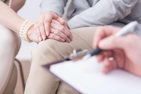 Primer plano de las manos de pareja se casó en una actitud cariñosa y un Flipboard borrosa con alguien escribiendo en él