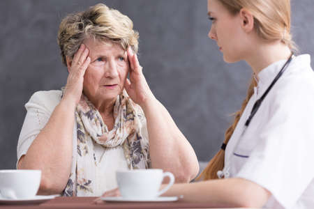 home visit: Ill senior woman with headache and medic during home visit, sitting beside table and drinking coffee