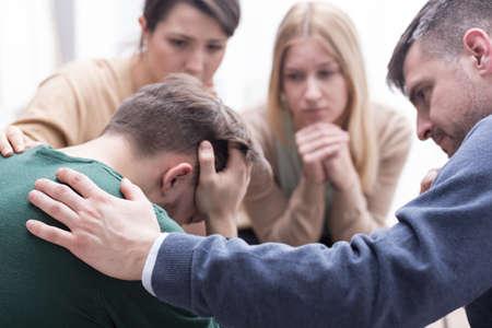 Primer plano de un joven devastado con la cabeza entre las manos y un grupo de amigos en una pose de apoyo a su alrededor Foto de archivo