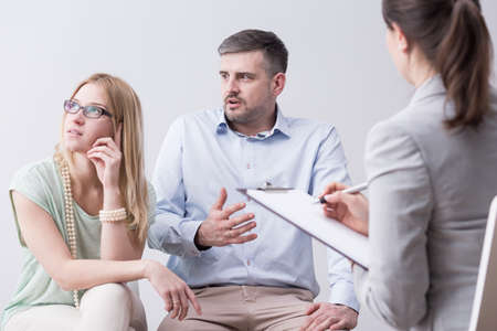 couples therapy: Shot of a young man talking angrily to his resentful wife during a couples therapy session