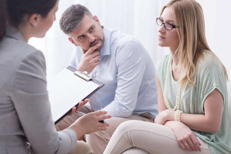 Mujer joven trastornada hablar con un psicólogo femenino, con su marido a un lado Foto de archivo