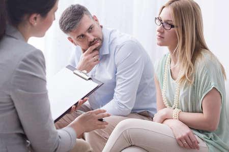 Verstoor jonge vrouw te praten met een vrouwelijke psycholoog, met haar man opzij