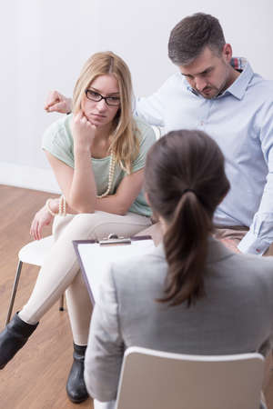 mediator: Young couple during a family therapy session, sitting in front of a counselor with a flipboard
