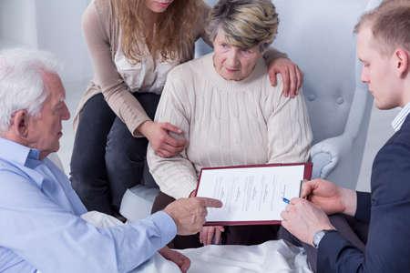 testament schreiben: Familie um das Bett eines kranken alten Mann zu sammeln, auf der Suche durch die Dokumente ist er zu unterzeichnen