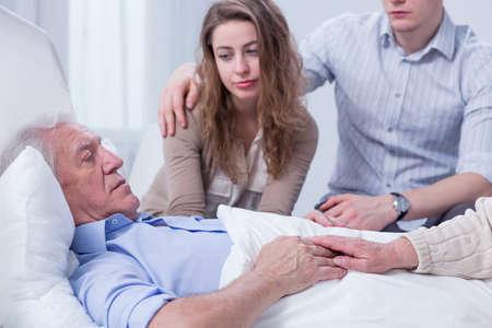 彼の孫と妻に囲まれた病院のベッドで横になっている老人