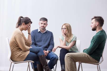 Disparo de cuatro seus jóvenes sentados en sillas en círculo, escuchando a uno de ellos hablando con su cara en sus manos Foto de archivo
