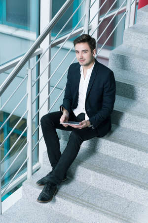 graduation suit: Good looking young man sitting on the stairs inside a modern office building, using his tablet