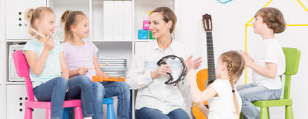 common room: Young woman playing the tambourine among four kids sitting on varicoloured plastic chairs Stock Photo