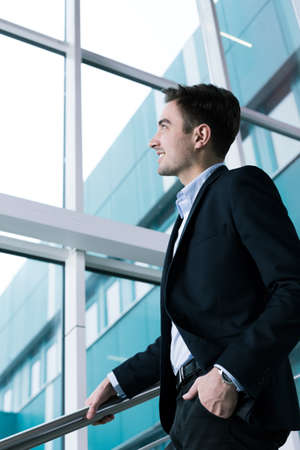 graduation suit: Elegant young man smiling and looking up while going down the stairs next to a glass wall of a modern building Stock Photo