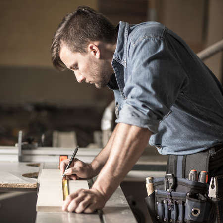 woodworker: Vertical view of young carpenter at work
