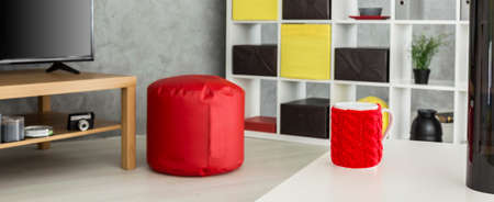 Modern grey interior with red pouffe, red cup standing on a white table, panorama