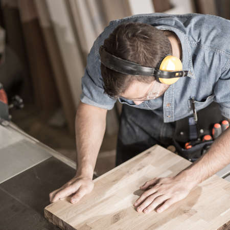 artisan: Photo of professional carpenter in muffs cutting board