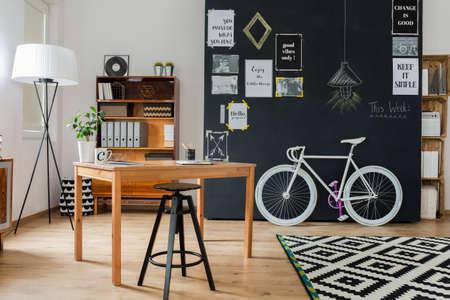 interior shot: Shot of a stylish studio interior with a minimalistic workspace and a big blackboard