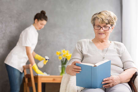 Elderly woman reading and caregiver cleaning her home