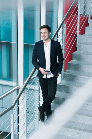 public building: Smiling elegant young man standing on the stairs inside a modern public building