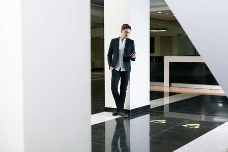 public building: Young man in a hall of a modern public building, using his mobile phone