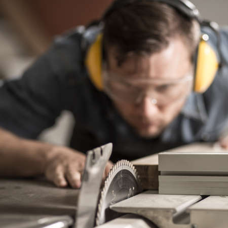Portrait of accurate joiner sawing wood using electric saw